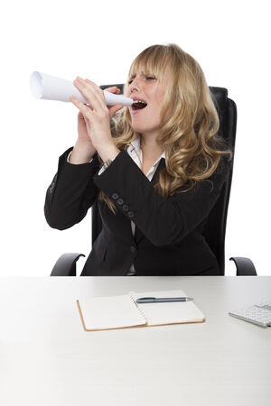 Laughing businesswoman playing with a paper roll in the office pretending it is a megaphone as she calls to her colleagues photo