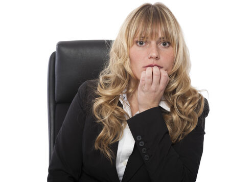 Businesswoman biting her nails in trepidation and fear as she anticipates a problem
