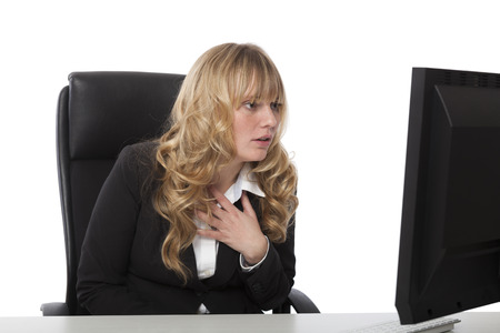 consternation: Attractive young blond businesswoman sitting at her desk staring in consternation at her computer monitor
