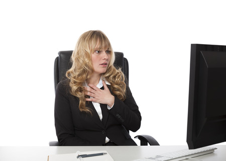consternation: Shocked businesswoman reading her desktop computer monitor as she sits at her desk with her hand to her chest with a look of consternation Stock Photo