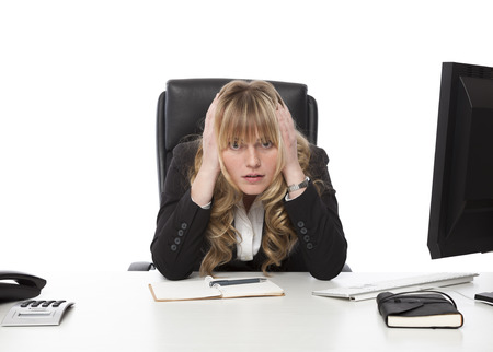 Depressed businesswoman at her wits end sitting morosely at her desk with her hands to her head staring balefully at the camera