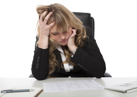 concentrates: Female business executive studying a report at her desk rumpling her hair with her hand as she concentrates on the contents Stock Photo