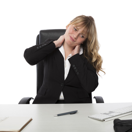 Pretty young female office worker with a stiff neck stretching and grimacing as she sits at her desk