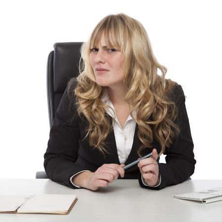 Confused zakenvrouw met een verbaasde frons peering zijwaarts naar de camera als ze probeert om zinvol van iets of begrijpen een collega