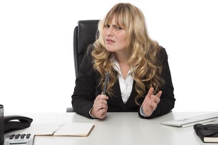 quizzical: Empresaria joven rubia atractiva con una expresi�n burlona mirando de reojo a la c�mara en la confusi�n mientras lucha por comprender algo Foto de archivo