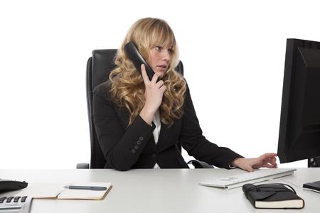 verlobt: Junge Geschäftsfrau Multitasking wie sie sitzt an ihrem Schreibtisch im Chat am Telefon während sie weiterhin auf ihrem Desktop-Computer eingeben