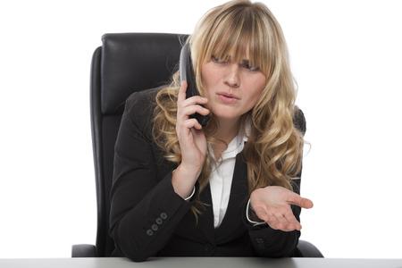Confused zakenvrouw fronsen als ze babbelt aan de telefoon op het werk vraagt om duidelijkheid een een bepaald punt, terwijl gebaren naar haar verbijstering te tonen