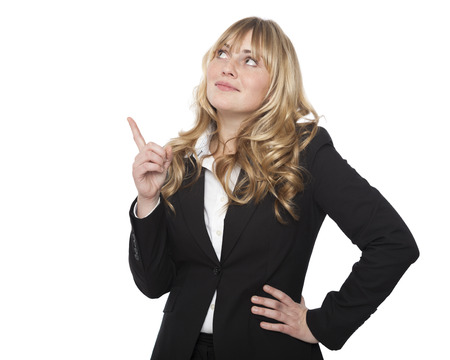 Attractive blond businesswoman pointing above her head towards blank copyspace with her finger with a cute smile, isolated on white photo