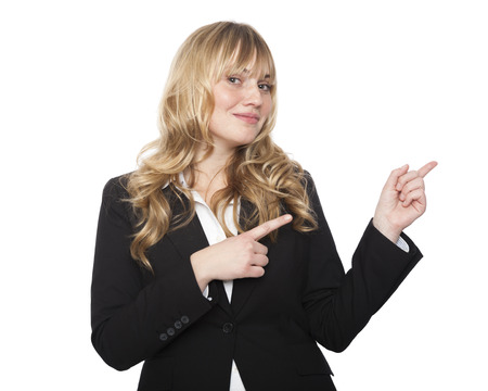 Friendly stylish young saleslady or businesswoman pointing with both hands towards the right of the frame and blank copyspace