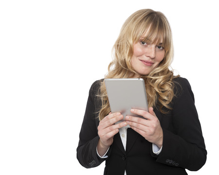 Smiling attractive young blond businesswoman holding a tablet computer in her hands smiling at the camera, upper body isolated on white photo