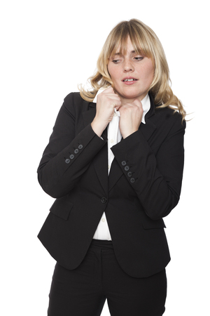 uncomfortable: Uncomfortable businesswoman tugging at her collar and looking down in trepidation showing she is nervous or because the collar of her shirt is too tight, isolated on white
