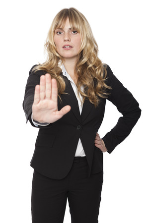 Businesswoman giving a halt gesture with the palm of her hand as she calls a halt to proceedings or forbids entry on a privacy basis, isolated on white Standard-Bild