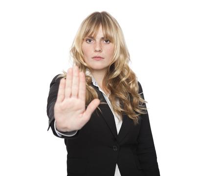 Stern aantrekkelijke blonde onderneemster het maken van een stop gebaar met haar hand met de palm naar voren om dat item weer te geven wordt verboden of tot stilstand te bellen als een tijd deadline verstrijkt