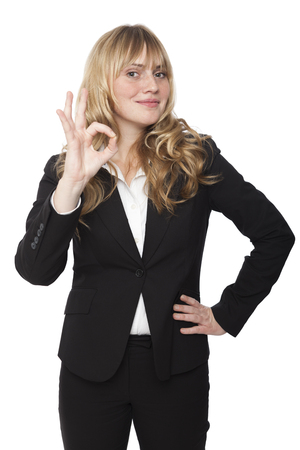 Stylish businesswoman making a perfect gesture with her fingers as she indicates that everything is of the best quality or has gone according to plan, isolated on white photo