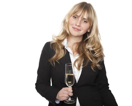 Attractive stylish young businesswoman at a company party or function holding a flute of sparkling champagne in her hand and smiling at the camera, isolated on white photo