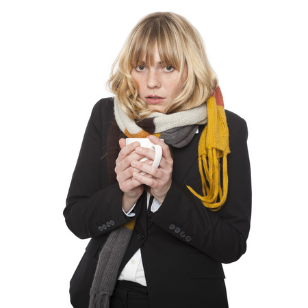 Cold miserable young woman hunkering down in her scarf clasping a mug of steaming hot soup or coffee in her hands, isolated on white Stockfoto