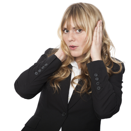 Businesswoman covering her ears pretending not to listen while at the same time leaning across with an intrigued expression, isolated on white photo