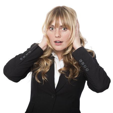 Woman covering her ears with her hands with a shocked expression as she tries to block out a sound or words that someone is saying, isolated on white photo