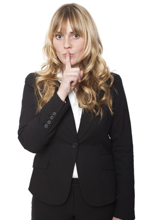 Beautiful young woman making a shushing gesture as she raises her finger to her lips asking for silence or that the viewer join her in keeping a secret, isolated on white Stock Photo