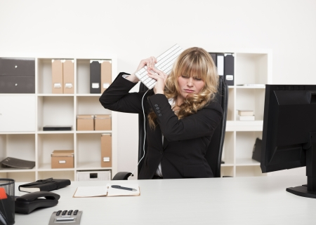 Angry businesswoman throwing a tantrum lifting her computer keyboard in the air as though about to strike her desk with it