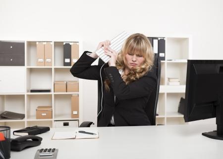Boze onderneemster gooien van een woedeaanval tillen haar computer toetsenbord in de lucht alsof het punt om haar bureau te slaan met het Stockfoto