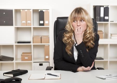 Nadenkend bezorgd zakenvrouw haar nagels te bijten en op zoek naar de kant met een ernstige nadenkende uitdrukking als ze anticipeert problemen