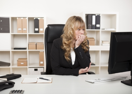 Thoughtful businesswoman sitting at her desk in the office reading her monitor on her desktop computer with her chin resting on her hand