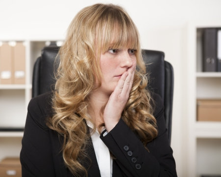 mistake: Young businesswoman looking worried with her hand to her face in consternation as though realising she has made a mistake Stock Photo