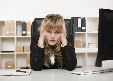Businesswoman at her wits end sitting at her desk in the office holding her head in both hands and glaring at the camera photo