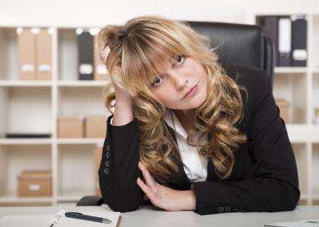 Bored mooie jonge zakenvrouw zit aan haar bureau in het kantoor met haar hoofd rustend op haar handen en een indruk ernstige uitdrukking