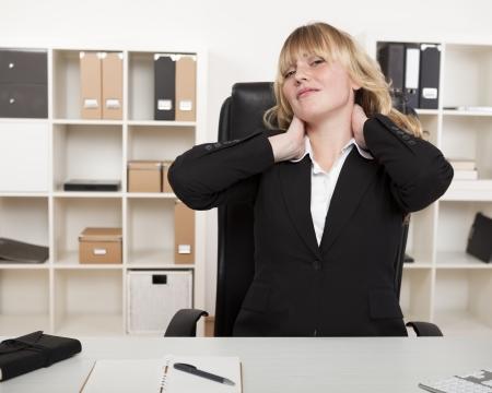 Overwerkt zakenvrouw stretching haar nek als ze zit op haar bureau in het kantoor aan de stam van de hele dag zitten te verlichten