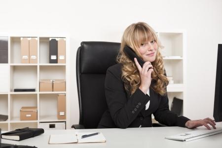 Vriendelijke stijlvolle jonge blonde vrouw zit op haar bureau in het kantoor kletsen aan de telefoon en lacht naar de camera Stockfoto