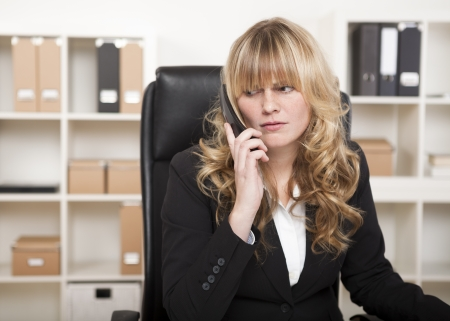 concentrates: Pretty businesswoman listening to a phone call sitting at her desk with a serious expression as she concentrates on what is being said, natural pose