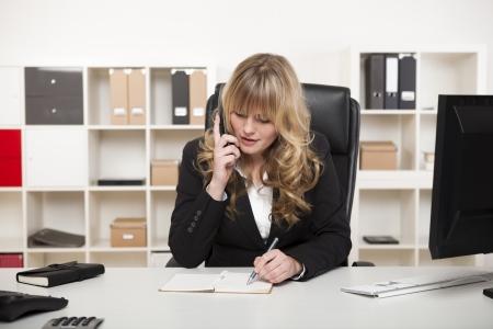 Aantrekkelijke blonde zakenvrouw of uitbaatster chatten op de telefoon in het kantoor als ze zit aan haar bureau te nemen notities als ze luistert naar het gesprek Stockfoto