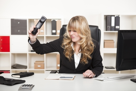 Beautiful young blond businesswoman slamming down the phone in her office after an argumentative phone call or in frustration