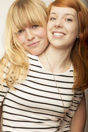red and blond haired girls friends laughing and hug Stock Photo
