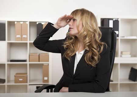 far away look: Young blond businesswoman sitting at her desk in the office, with her hand raised to her forehead staring into the distance waiting. Stock Photo