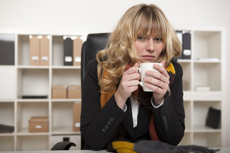 Cold businesswoman warming up with a mug of hot coffee as she sits at her desk, in the office wearing a knitted winter scarf. Standard-Bild