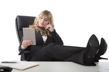Relaxed business woman holding a tablet reading with her feet up the table photo