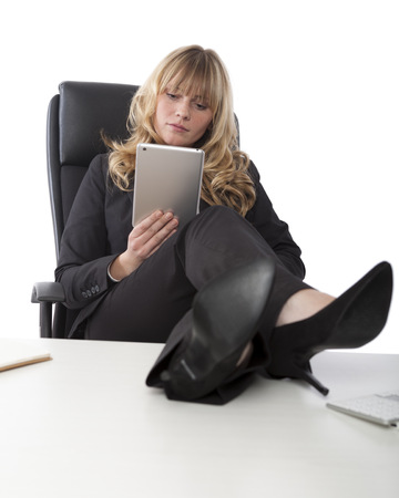 Relaxed businesswoman wearing stylish high heels with her feet on the desk sitting back reading her tablet-pc photo