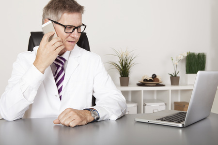Doctor chatting on his mobile phone while seated at his desk in his office reading information on the screen, of his laptop computer. Standard-Bild