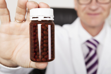 Doctor or pharmacist holding an unlabeled brown plastic bottle of tablets or medication towards the camera with selective focus to the container