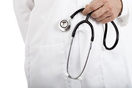Doctor holding a stethoscope in his hand dangling in front of his white lab coat, close up view of his stomach and hand. photo
