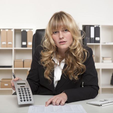 quizzical: Empresaria joven atractiva con una expresi�n burlona serio cuestionar un informe, mientras se�ala el papeleo, al tiempo que muestra figuras en una calculadora a la c�mara.