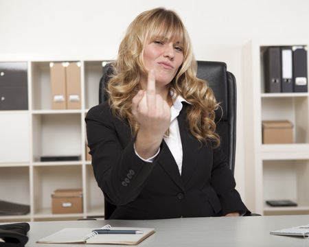 naughty woman: Pretty young blond businesswoman making a rude gesture with her middle finger at the camera, as she pulls a face showing her disgust.
