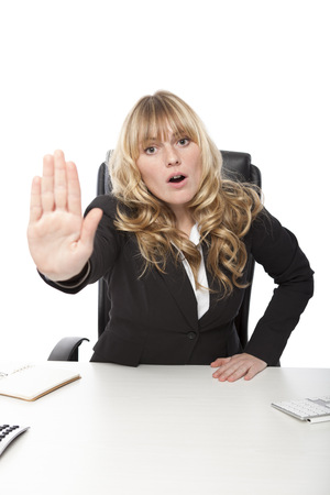 Jonge zakenvrouw zeggen - geen - houdt haar hand in een stop gebaar als zij noemt een einde te maken aan vervolging of vertelt iemand om weg te gaan, op wit