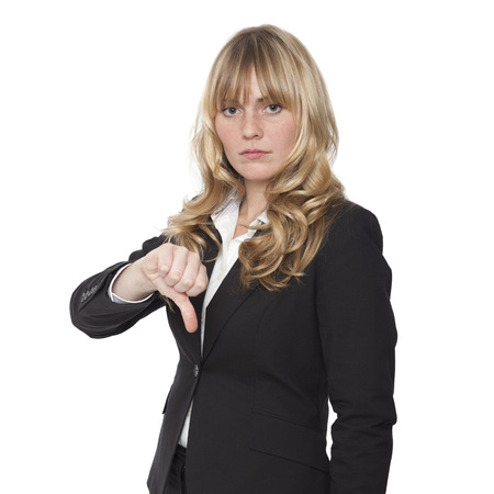 Businesswoman giving a thumbs down gesture indicating a failure or voicing her displeasure and negative views, on white. photo