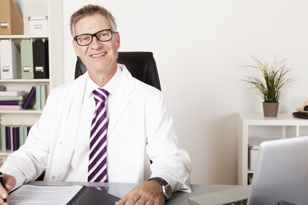 Happy Male Physician Looking at Camera While Sitting Down at his Office Standard-Bild