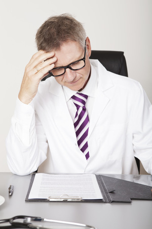 Male Health Professional Seriously Reading Reports on Table photo