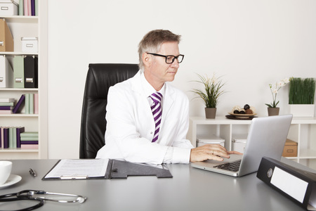 doctor laptop: Male Doctor Using Laptop for Medical Reports Stock Photo